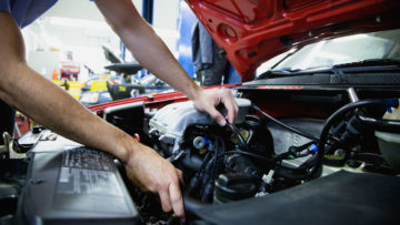 AE8XYW Close up of male auto mechanic working on engine in auto repair shop